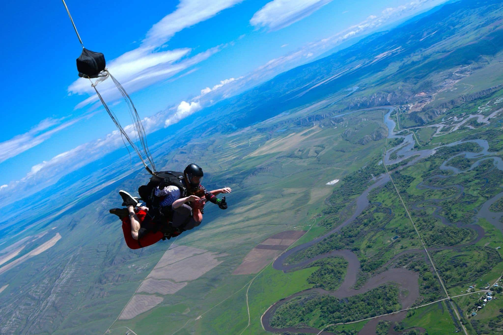 Tandem instructor and female student in freefall above green landscape